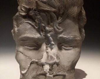 Glass art face sculpture, falling apart, sand cast portrait of a man, happy accident