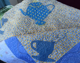 A tea party table cover or a little girl's keepsake quilt. Applique tea pots and cups, blue and yellow.