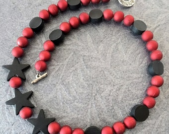 Necklace 19 inches a-symetrical black vinyl stars, black wood discs and red plastic/vinyl beads with silver star burst toggle clasp