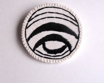 Textile geometric brooch hand embroidered in black and cream on cream muslin with a cream felt backing An Astrid Endeavor