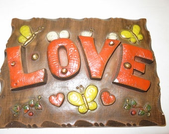 Large Wall Hanger. LOVE with flowers butterflies. 11x9 with wire hanger in the back for displaying. Nice Vintage piece.