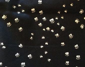 Black cotton fabric with white paw prints.