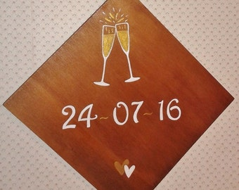 Wooden plaque handpainted with wedding date sign and glasses.