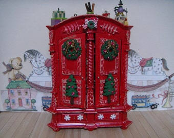 A red Christmas shabby toy cupboard for an old fashioned dolls house shop.