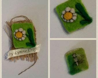 Needle felt daisy on a green background. Brooch.