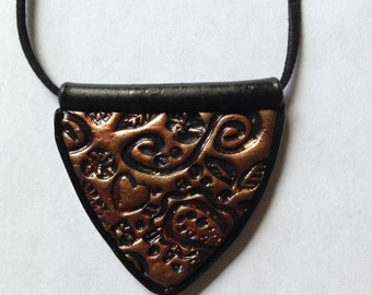 Shield pendant in bronze/black textured polymer clay