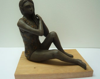 Sculpture of woman the bather on a wooden base