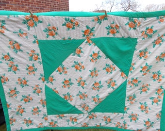 Vintage quilt, likely 1930's, Scottish.  Orange roses on light cream background, which has a small coiled black motif. Green accents panels.