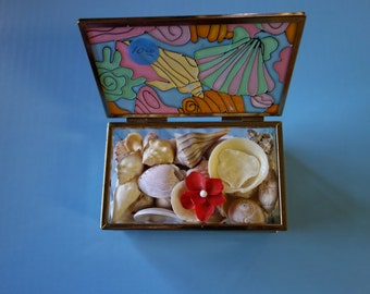 Painted glass and brasslike metal contain a treasure of seashells.  Also a fishscale crimson flower.