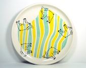 platter decorated with adorable Piglet prints, on a masked decorated surface of Blue Green and Yellow. Ready to Go.