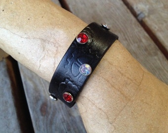 Black leather wristband with stamps and rivets