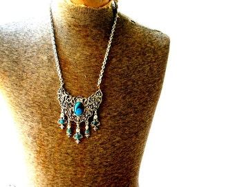 boho vintage 70s silver tone metal necklace with a large filigree pendant, tassel and faux turquoise.
