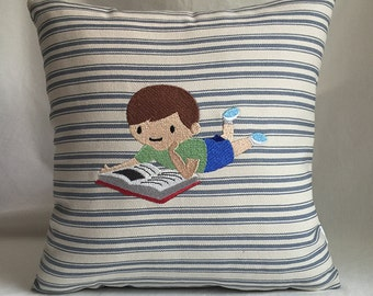 "Young boy reading 12""x12"" pillow, embroidered on striped fabric"