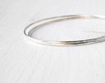 Set of 2 skinny bangles bracelets in silver / hammered stacking silver bangles / shiny silver slim hammered bangles /