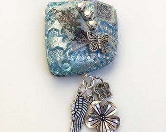 Blue and silver textured and embellished polymer clay pendant