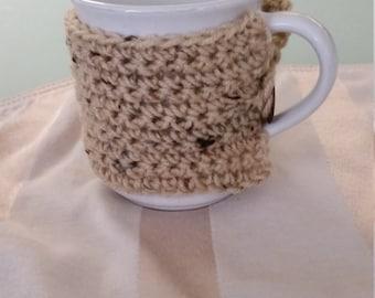 Crocheted coffee mug cozy in buff