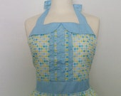 Retro apron with collar and ruffles, multi coloured polka dots on a white fabric.