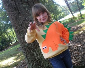 Children's applique dinosaur shirt with orange dinosaur with green spikes. Size medium only, dino shirt, reptile shirt, fun shirt, SPECIAL