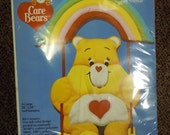 Vintage Care Bears  quilted wall hanging kit featuring Tender-heart Bear on a rainbow swing  from 1984 in the original packaging