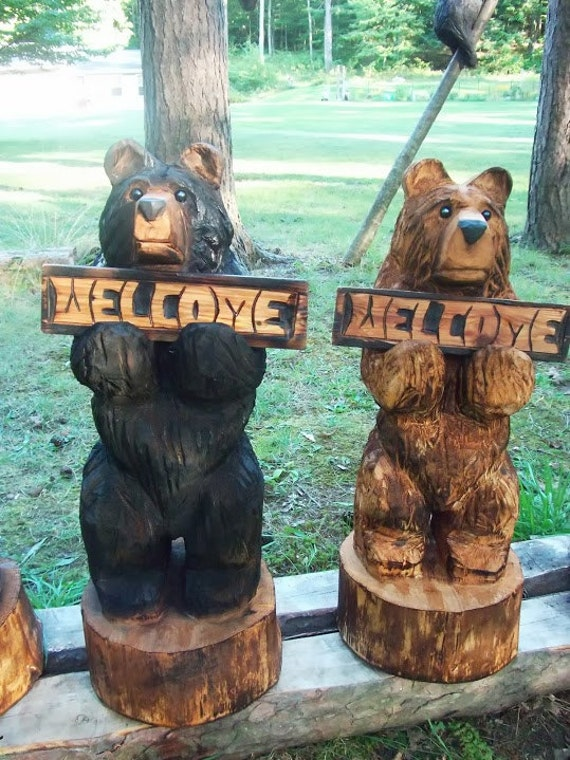 Chainsaw carved bear holding a welcome sign
