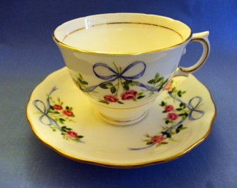 """VINTAGE Teacup & Saucer - White Bone China, Delicate stems of Pink Roses tied together with Blue Ribbon, scalloped rims, gold trim """"England"""""""