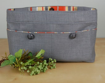 """Walker Bag:  Steel gray """"textured"""" bag with bright orange, white and gray striped lining, and antique buttons."""