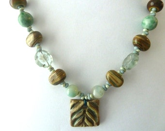 handmade green and cream ceramic leaf and lampwork necklace, UK sterling silver jewellery