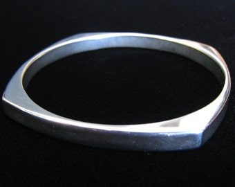 "Modernist Stainless Steel Near Square Bangle Bracelet is 1/4"" Wide with Round Center Space and Squared Corners."