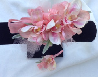 Corsage and matching boutonniere in coral orchids