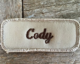"Cody. A metallic tan work shirt name patch that says ""Cody"" in brown script"