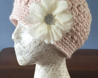 Crochet pink woman hat with a cream flower.