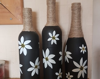 Set of 3 handmade, upcycled, black wine bottles, painted with daisies and wrapped with twine