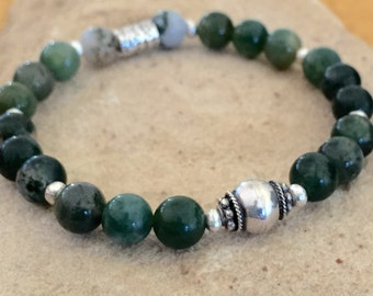 Green bracelet made with agate beads, Hill Tribe silver rondelles beads, a sterling silver bead and a sterling silver tube bead on elastic