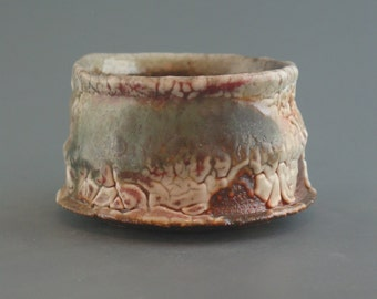 Teacup, wood-fired iron rich stoneware with crawling shino, oribe and natural ash glazes