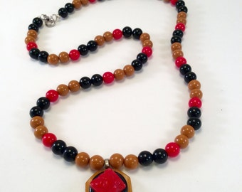 Stacked button pendant in red, black and butterscotch on lucite necklace