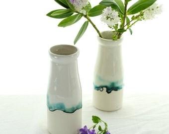 Interior room decor. Ceramic vase, milk bottle bud vase with landscape painting in glazes. Ceramic white vase. Contemporary interior design.