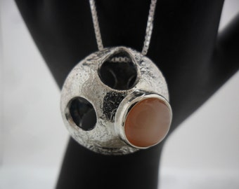 Biconvex reticulated silver pendant decorated with a moon stone fishing