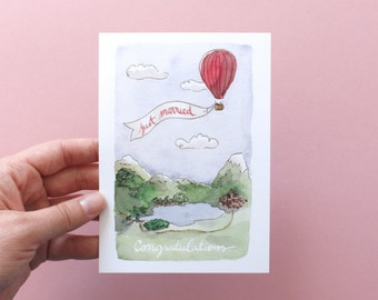 Congratulations card for a wedding. Watercolor drawing ballooning and mountains. Text : Just married and congratulations. A6