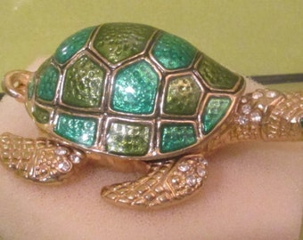 Turtle with Flip Up Shell.  SMALL.  Inside is a Goldtone Figure of a Child  Holding a Cross--Austrian Crystal with Amethyst Stone