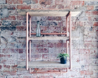Copper pipe shelving with distressed industrial style scaffolding planks. Copper frame is polished with a metallic finish.