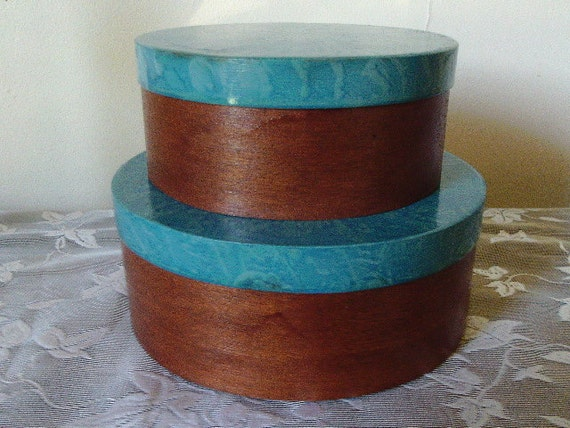 Two shaker boxes with lids vinegar painted in teal.