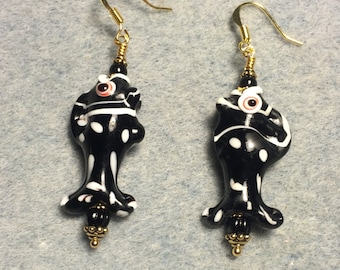 Black and white spotted lampwork fish bead earrings adorned with black Czech glass beads.