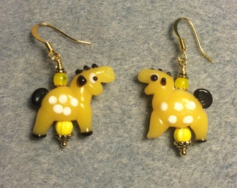 Opaque spotted yellow lampwork horse bead earrings adorned with yellow  Czech glass beads.