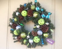 Pickeball Christmas wreath, up cycled pickle balls and faux evergreen foliage adorned with natural pinecones and blue and silver ornaments