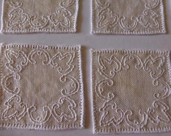 Eight natural linen appliques embroidered with white thread