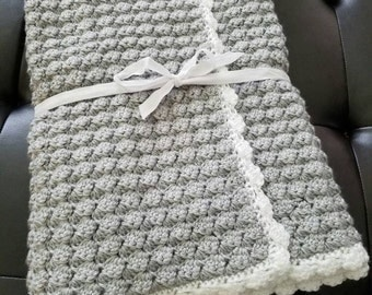 Crocheted baby blanket with puff stitch and scalloped border