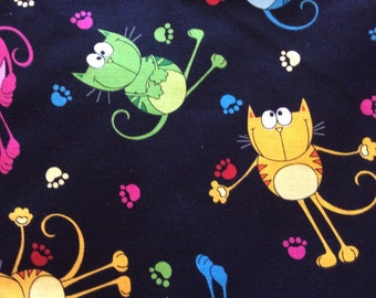 Timeless treasures 2007 Patt # CAT-C 2556 . Black background with bright colored cats and paw print.