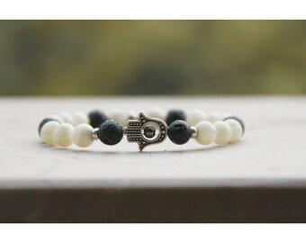 Handmade bracelet in semiprecious stones black lava and white with Hamsa hand.