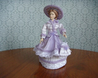 1/12th miniature scale wigged resin doll with moveable head and limbs,dressed in lilac silk