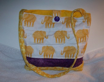 Elephants march across this purse in  golden yellow with accent of purple, perfect for everyday or a special occasion. p101y